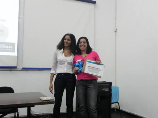 A estudante de Pedagogia, Magda Rangel, recebendo o prêmio pela participação na construção do logo do evento, que pode ser visto na imagem a seguir.